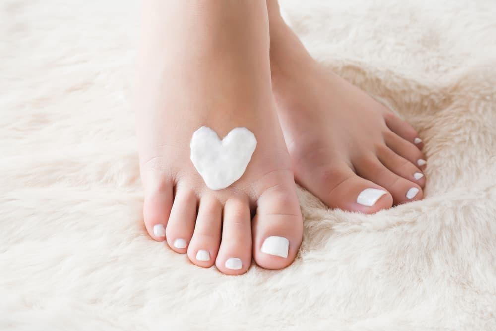 כפות רגליים מטופחות של אישה עם לב עליהן