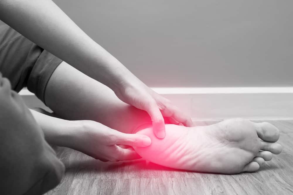 אישה אוחזת ברגלה עם כאבי דורבן בכף הרגל
